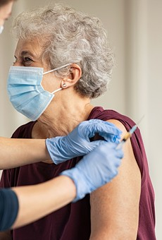 Doctor giving injection to senior woman at hospital.