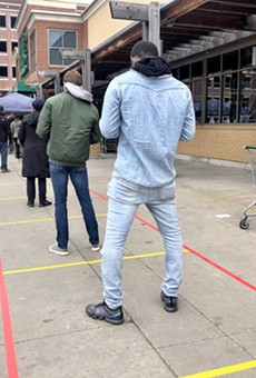 Social distancing markers guide an overflow line outside the Detroit Whole Foods store.
