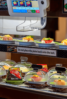 A conveyor belt delivers plates of sushito customers.