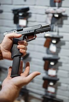 Man choosing new handgun in gun shop.