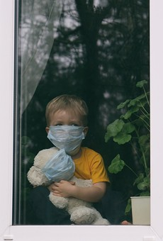 Sad child in protective medical masks looks out the window.