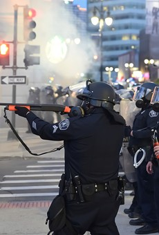 Detroit police officer fires at protesters.