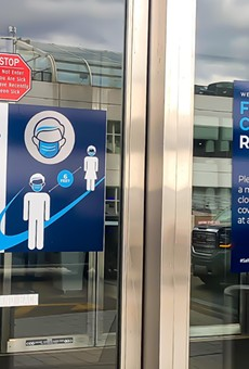Entrance door of DTW terminal building with sign requiring masks.