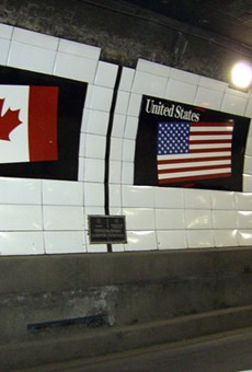 Flags of Canada and the United States over a metal boundary marker in the Detroit-Windsor Tunnel.