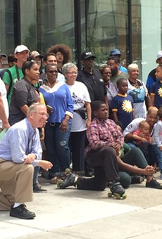 Longtime Detroiters pose for photo in front of building where racially controversial Bedrock ad was taken down.