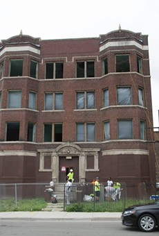 Crews on site at 2447 Cass, which housing preservationists say is slated for demolition.