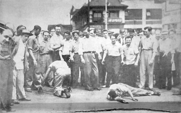 White rioters swagger over their black victims in front of a gas station at Erskine and Woodward in this newspaper photograph. - UNIDENTIFIED CLIPPING, 1943 RIOT FOLDER, BURTON COLLECTION, DETROIT PUBLIC LIBRARY