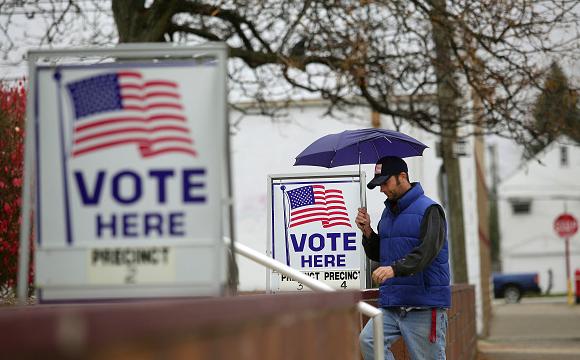 A man walks into a precinct on a rainy election day, his umbrella broken. - SHUTTERSTOCK