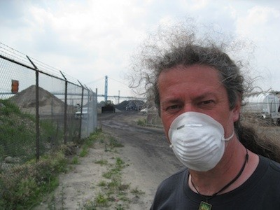 A protester stands in front of the piles of petcoke that graced the riverfront in 2013. The piles have since been removed. - PHOTO BY CURT GUYETTE