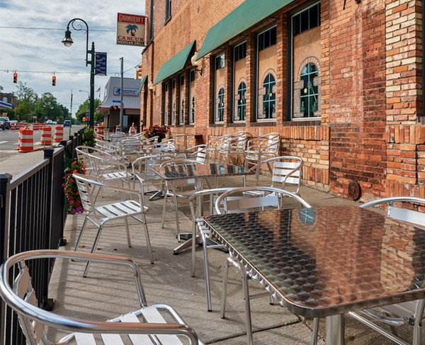 View of outside patio furniture for the Cancun Mexican Grill and the Grand Loft business at the corner of Bridge Street and Jefferson in Grand Ledge. - FOCUSED ADVENTURES / SHUTTERSTOCK.COM