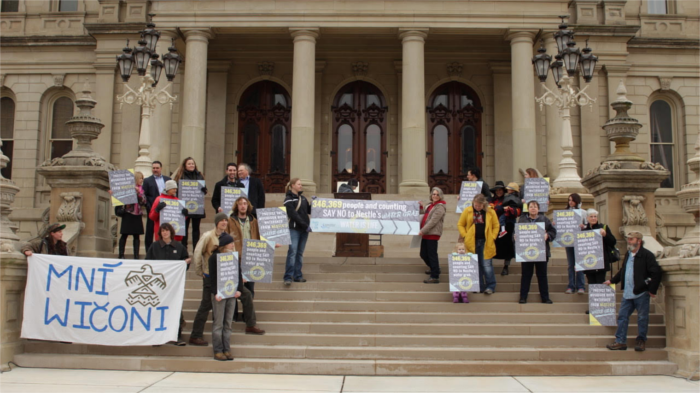 Bearing banners and signs, activists made quite a show of delivering a massive petition against the water giant's plans to pump more out of Michigan. - COURTESY MCWC