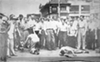 White rioters swagger over their black victims in front of a gas station at Erskine and Woodward in this newspaper photograph.