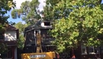 Guy climbs on roof in protest of demolition of neighboring house
