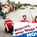 Wage theft protesters stage a sit-down protest to block the entrance of the Walmart distribution center in Elwood, Ill.