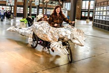 PHOTO BY DOUG COMBE. - 826Michigan Executive Director Amanda Uhle pilots the pangolin bike, during a test run at the Eastern Market.