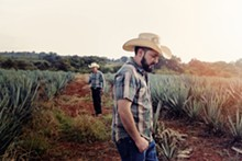 PHOTO BY CYBELLE CODISH - Antonio Lopez with his father, Silverio, in the background on their agave farm in the Los Altos region in the Mexican state.