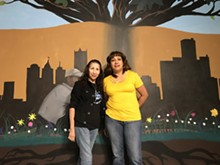 ALYSA ZAVALA-OFFMAN - Cleaning in Action founders Carolina Torres and Maria Perez in front of a mural inside Grace in Action.