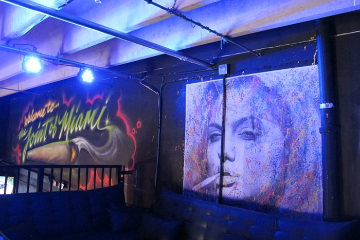 The entrance to the lounge is decorated with murals that glow beneath blue lights. - PHOTO BY NATALIA GALICZA