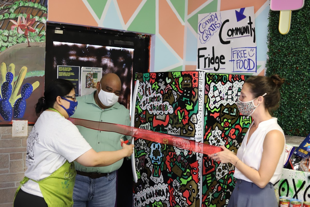 Buddy System activists Diana Resendiz, Gilberto Zepeda, and Kristin Guerin unveil a community fridge in Homestead.