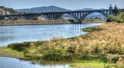 PHOTO BY BARRY EVANS - A 1932 seven-arch prestressed concrete bridge takes Highway 101 across the Rogue River at Gold Beach, ORE. Each arch spans 230 feet.