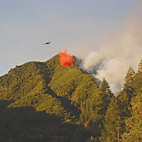 Our Fire, Our Fight A bomber drops fire retardant on what was hoped to be the unburned side of the East Peak fire line as firefighters ignite the other side. Photo by Ben Beaver
