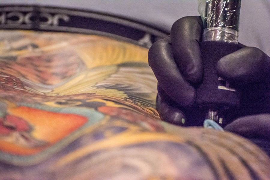 """A close-up view reveals the artist's tattoo gun at work on the the """"canvas"""" of a person's back. - MARK LARSON"""
