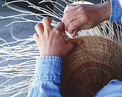 A Hoopa/Yurok weaver makes an acorn cooking basket from hazel sticks and spruce roots (which swell when wet to make a waterproof basket for cooking). Photo by Jennifer Kalt