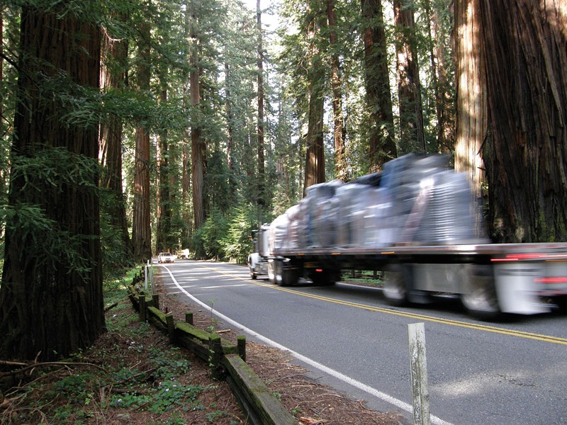 """A truck barely stays inside the line while rounding the curve between mile post markers 1.35 and 1.40. The area on the right is where Caltrans proposes a """"sliver fill."""" - PHOTO BY DAVID BERGIN"""