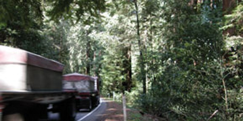 "Roads and Redwoods A truck barely stays inside the line while rounding the curve between mile post markers 1.35 and 1.40. The area on the right is where Caltrans proposes a ""sliver fill.""  Photo by David Bergin."