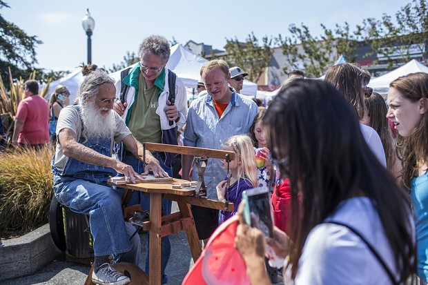 A woodworker demonstrates his hand crafted pedal scroll saw for a crowd at the North County Fair. - ALEXANDER WOODARD