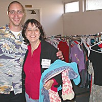 Everyone Is Connected Alexander Brewer, happy all day because he's helping people gather up fresh clothes, and one of the Project Homeless Connect organizers, Elizabeth Conner. Photo by Heidi Walters