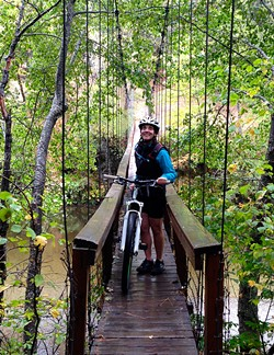 PHOTO BY JON O'CONNOR - Amy Cirincione, beginning her ride at a suspension bridge that crosses the Trinity River.