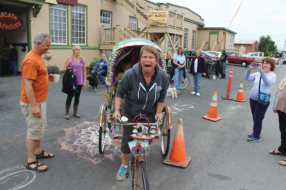 At the new Creamery District Art Market held Saturday, May 31, Jackie Dandeneau of the Arcata Playhouse makes way on her Indian pedicab while market coordinator Louis Hoiland looks on. - PHOTO BY BOB DORAN