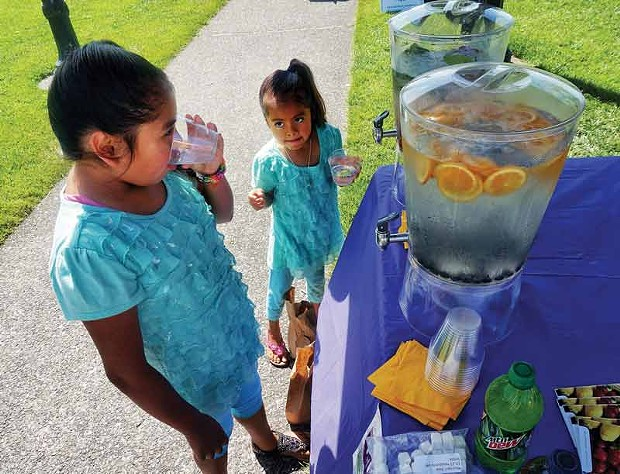 Azuanny and Cynthia guzman sample cool water flavored with fruit comparing it with sugary beverages in a booth for the WIC nutrition program at the Arcata Farmers' Market, Saturday, July 26. - PHOTO BY BOB DORAN.