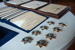 PHOTO BY MARK MCKENNA - Badges for new and promoted Eureka Police Department officers sit ready or pinning on a table at the Wharfinger on Wednesday.