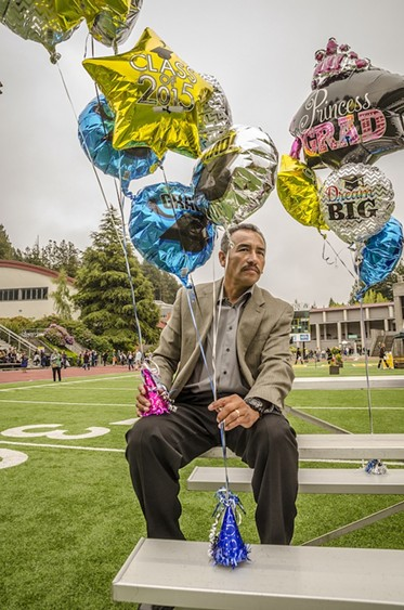 Balloon-laden Bernabe Casanova, of Berkeley, awaited the entrance of his daughter Viridiana Casanova Barrera, a history major, into Redwood Bowl. - MARK LARSON