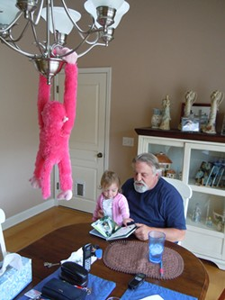 PHOTO BY HEIDI WALTERS - Carl Young and his granddaughter Emily enjoy an animals book.