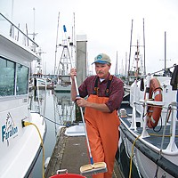 Two If By Sea Charter boat skipper Tim Klassen scrubs down the Reel Steel at Woodley Island Marina after another day out on the ocean with some sport fishing clients. Photo by Heidi Walters