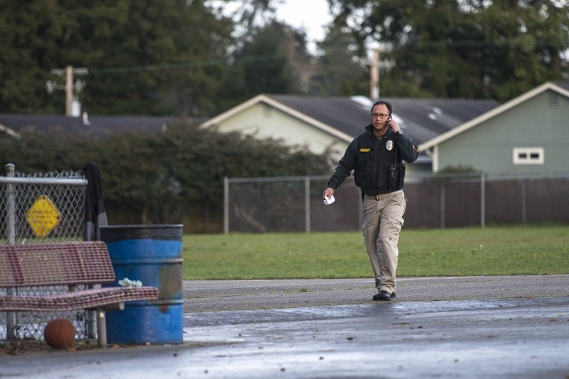 Sheriff's Lt. George Cavinta talks on the phone at a field near Cutten Elementary School, where officers were looking for a discarded firearm that may have been used in this morning's homicide. - MARK MCKENNA