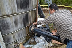 PHOTO BY GRANT SCOTT-GOFORTH - Erick Arcos points out leaks and temporary repairs to Alderpoint's faltering water tanks.