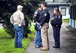 Eureka police officers stand by as tenants move out of the Blue Heron Lodge on Broadway, which was condemned by the city this morning. - MARK MCKENNA