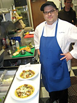 F St. Cafe Chef Dan McHugh puts finishing touch on seared scallop entrees. Photo by Bob Doran.