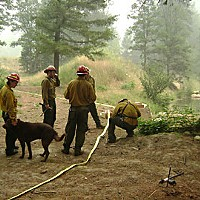 Fire Without End Firefighters run hoses and set up sprinklers to protect structures on private property in Corral Bottom. Photo By David Garrison