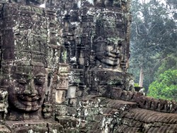 PHOTO BY BARRY EVANS - Four of more than 200 massive stone faces, perhaps in the likeness of the king who commissioned them, atop the Bayon temple in the Angkor Wat complex, Cambodia.