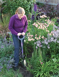GENEVIEVE SCHMIDT PLIES THE EARTH WITH HER RADIUS PRO GARDEN SHOVEL.