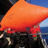 """Gunner's Mate 3rd Class David Jones, left, mans a .50-caliber machine gun while Aviation Ordnancemen throw an SUW-17 """"killer tomato"""" target over the side of the aircraft carrier USS John C. Stennis."""