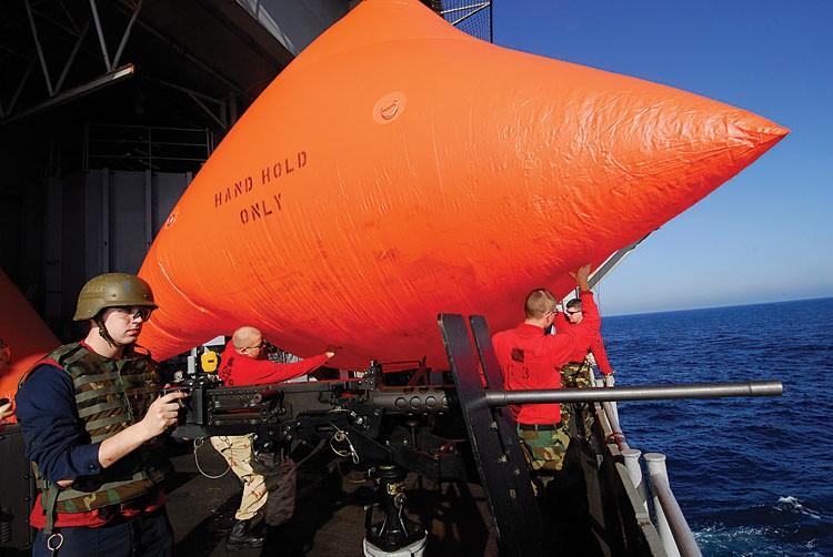 """Gunner's Mate 3rd Class David Jones, left, mans a .50-caliber machine gun while Aviation Ordnancemen throw an SUW-17 """"killer tomato"""" target over the side of the aircraft carrier USS John C. Stennis. - U.S. NAVY PHOTO BY MASS COMMUNICATION SPECIALIST 3RD CL"""