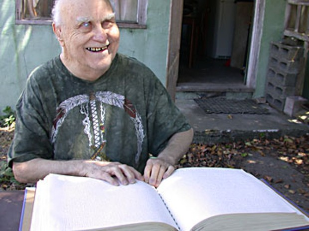 """Harvey Jossem, summer 2006, opens his braille dictionary at random. """"'Salient!'"""" He says. It was as if the dictionary — voluminous, supposedly obsolete — had chosen that word to be discovered that day. To make a point.  Photo by Heidi Walters"""