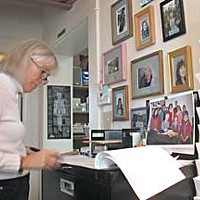 Wounded Healers HCBHP Client Services Director Sharon Nelson. The framed photos are a memorial to local women who've died of cancer. Photo by Helen Sanderson.