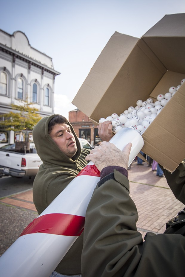 "Matt Casagrande of Eureka helps load the ping-pong balls into the ""snowball cannon"" made by Dean Kruschke. - PHOTO BY MARK LARSON, COURTESY MARK LARSON PHOTOGRAPHY"